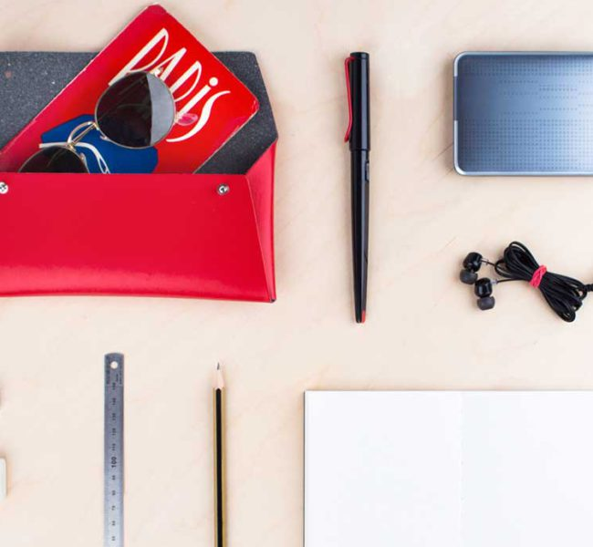 Red folder, black pen, headphones, plain paper pad, pencil, ruler, pencil sharpener, pencil eraser, and sunglasses.