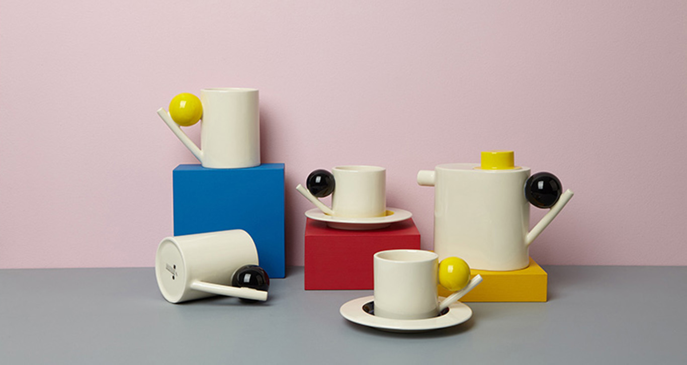 Four ceramic cups and a ceramic teapot displayed on coloured boxes in front of a pink background.
