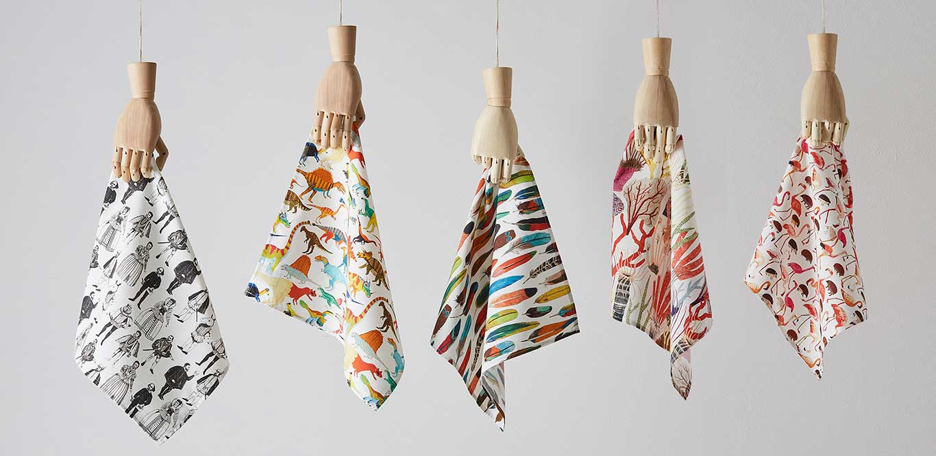 Five wooden hands hanging from string.Each hand is holding a multi coloured pocket square.