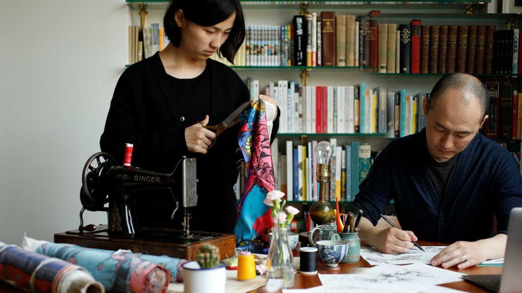A female artist cutting fabric with scissors while a male artist draws a sketch with a pencil.
