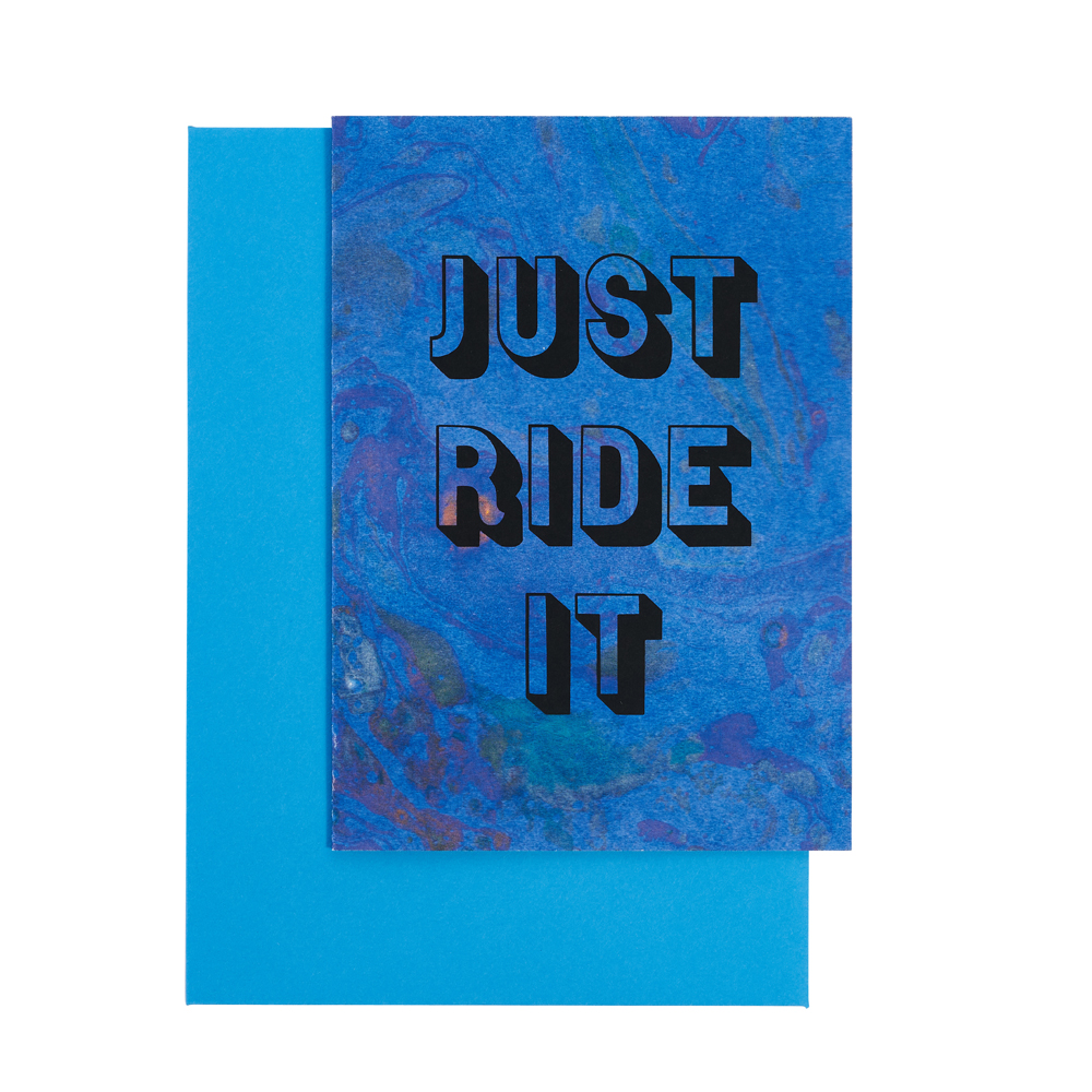 'Just Ride It' on blue marbled paper with a blue envelope