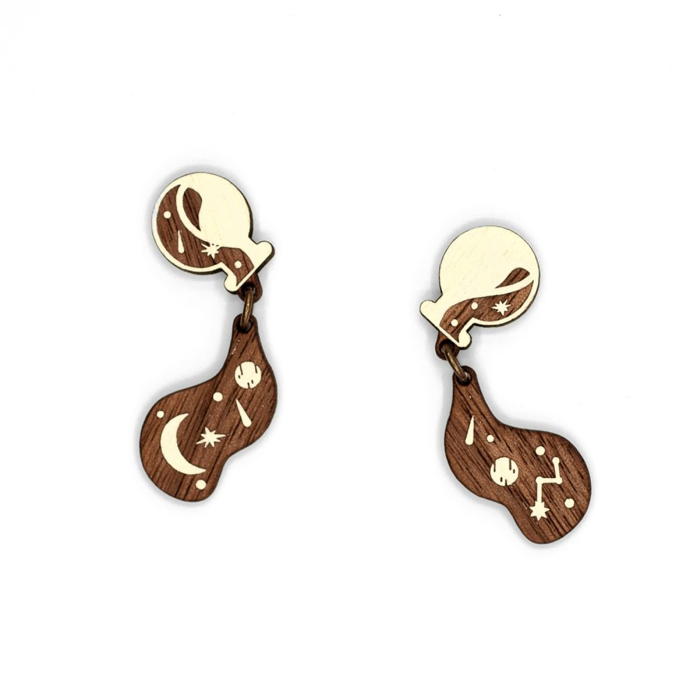 Pair of laser-cut wood earrings in the shape of spilled potions with stars.