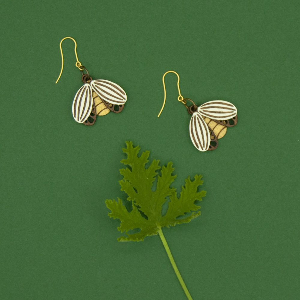 Woodcut beetle earrings set against a green background.