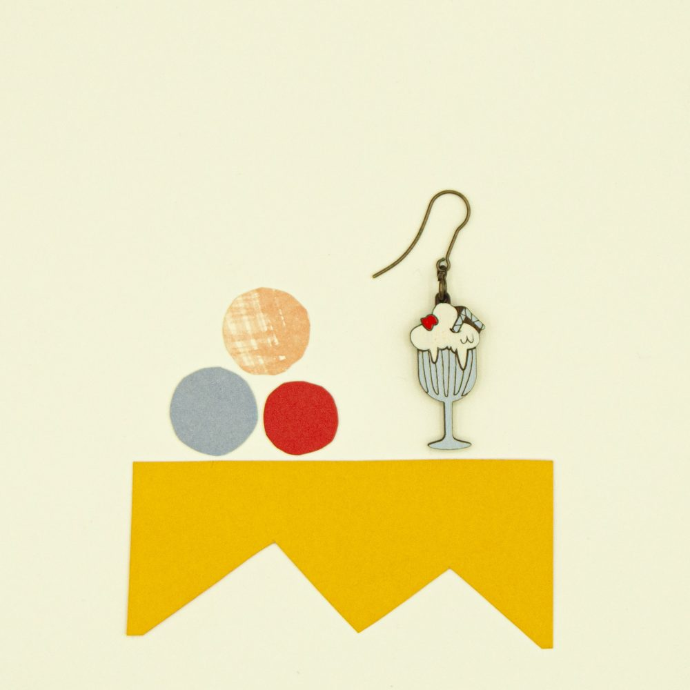 Lasercut wood milkshake earrings against a yellow background.