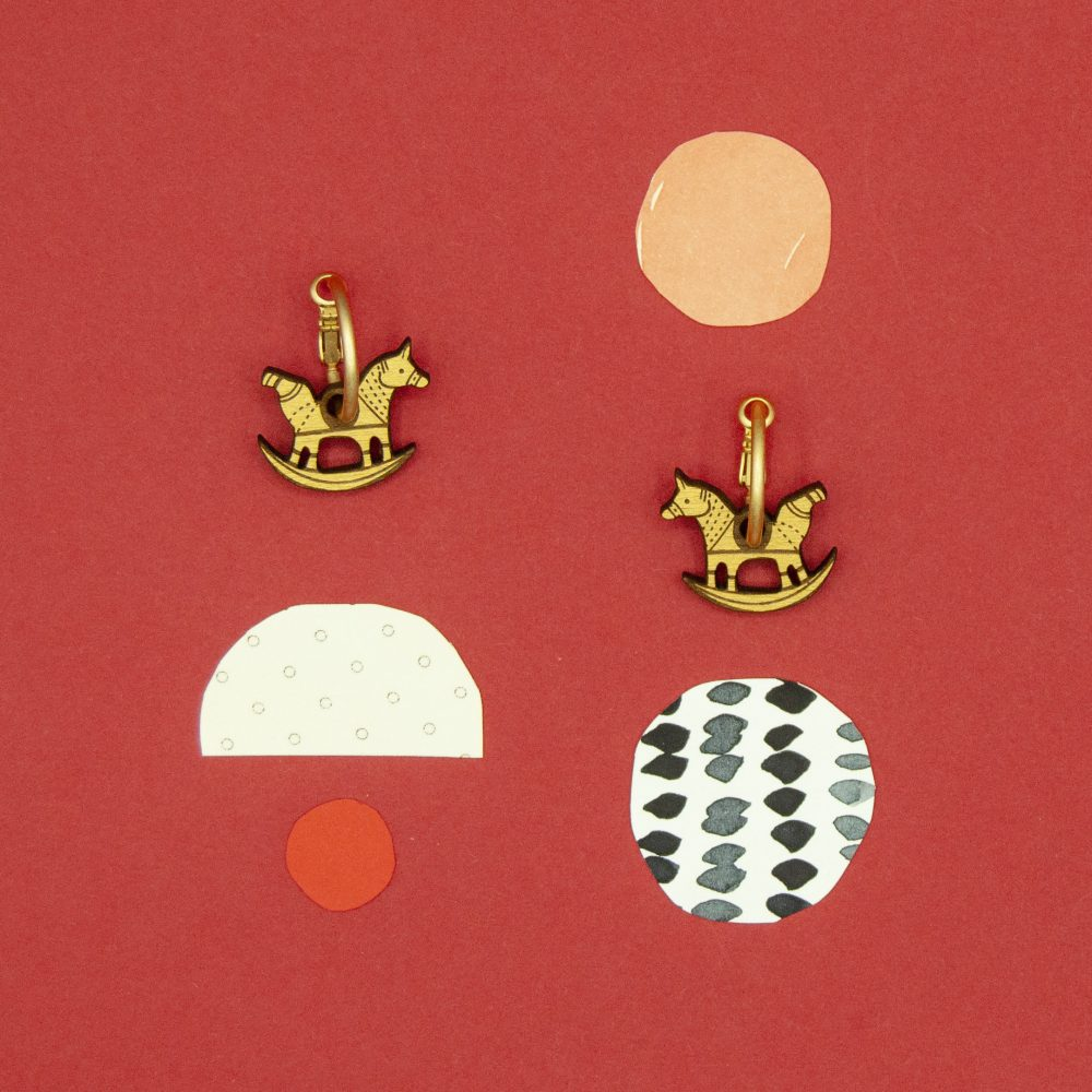 Lasercut wood horse earrings against a red background