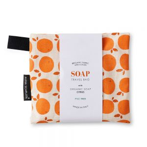 A travel bag with organic soap inside featuring an orange print.