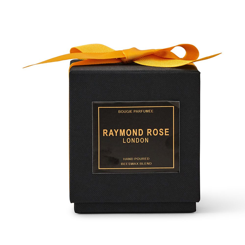 A candle in a black box with yellow ribbon..