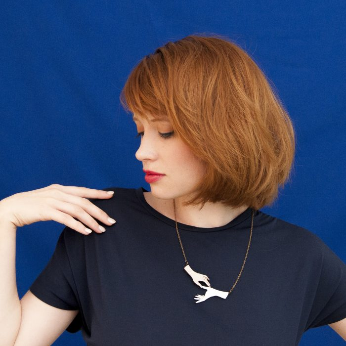 A female model wears a lasercut necklace against a blue background.