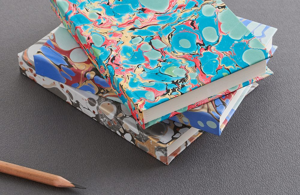 Stack of three marbled notebooks