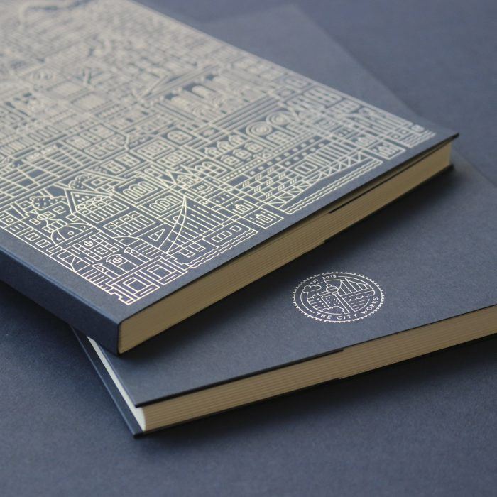 Close up photo of a navy blue notebook with silver foiled line illustration of London