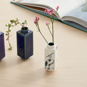 Three mini vases on a table with flowers and a book in the background