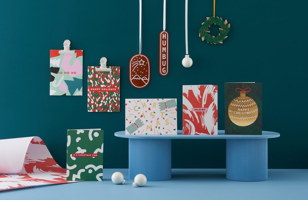 Selection of holiday cards and baubles displayed on a dark teal background