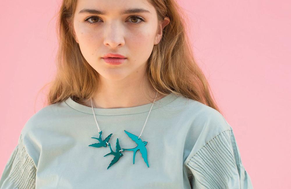 Woman wearing triple swallow necklace