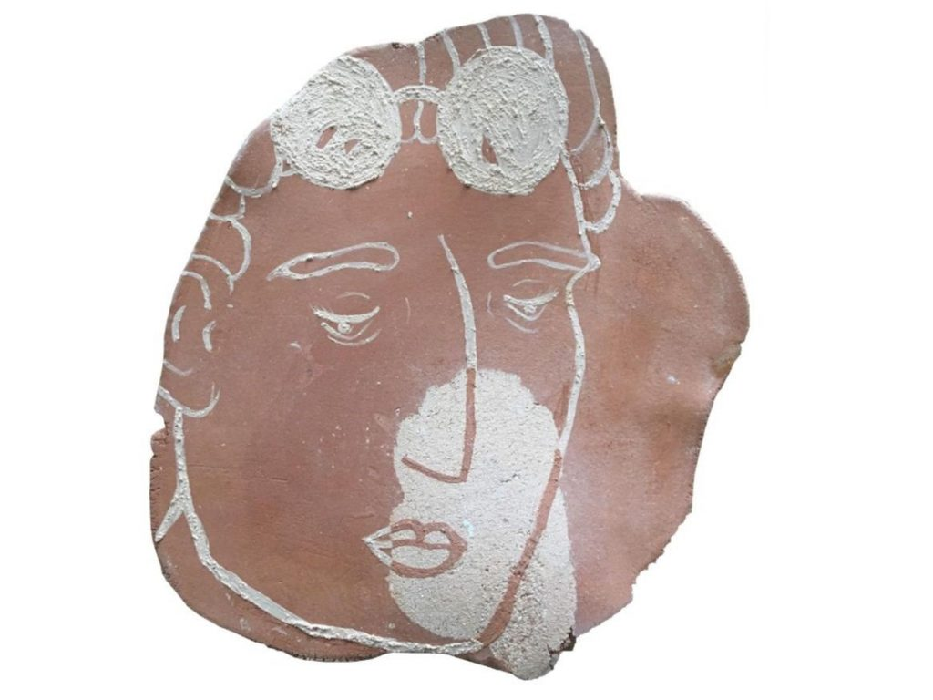 A terracotta piece of clay with an illustrated face on